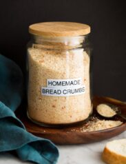 Image: homemade plain bread crumbs in a glass jar set on a wooden plate with a black background.