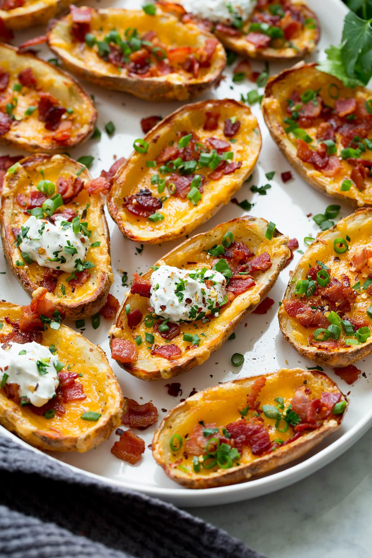 Potato skins shown from a side angle on a large serving platter.