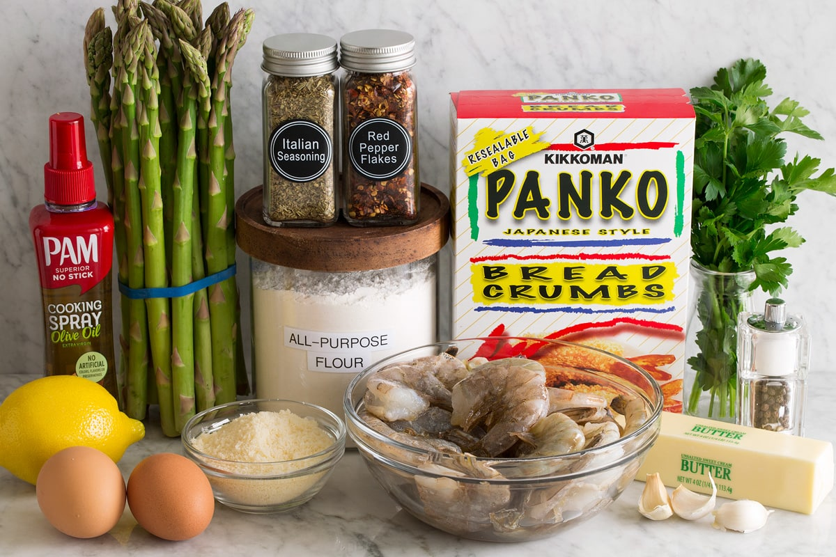 Photo of ingredients for sheet pan shrimp and asparagus. Includes raw shrimp, garlic, butter, salt, pepper, parsley, panko, flour, red pepper flakes, Italian seasoning, parmesan, eggs, lemon, asparagus and olive oil cooking spray.