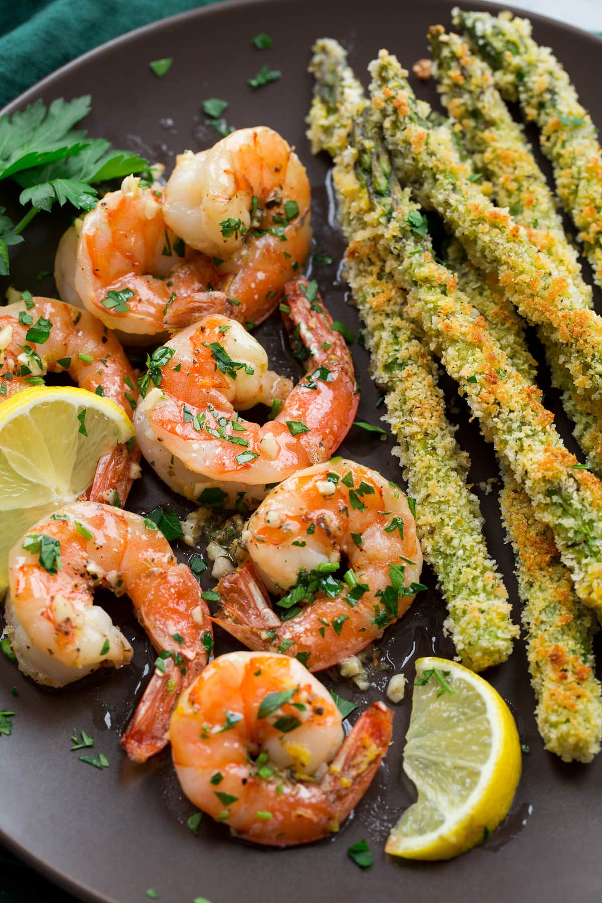 Close up image of shrimp and panko crusted asparagus on a dark brown plate.