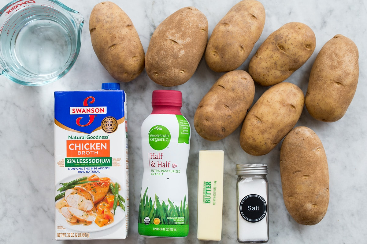 Photo shows ingredients used to make crockpot mashed potatoes. Includes russet potatoes, butter, salt, half and half, chicken broth and water.