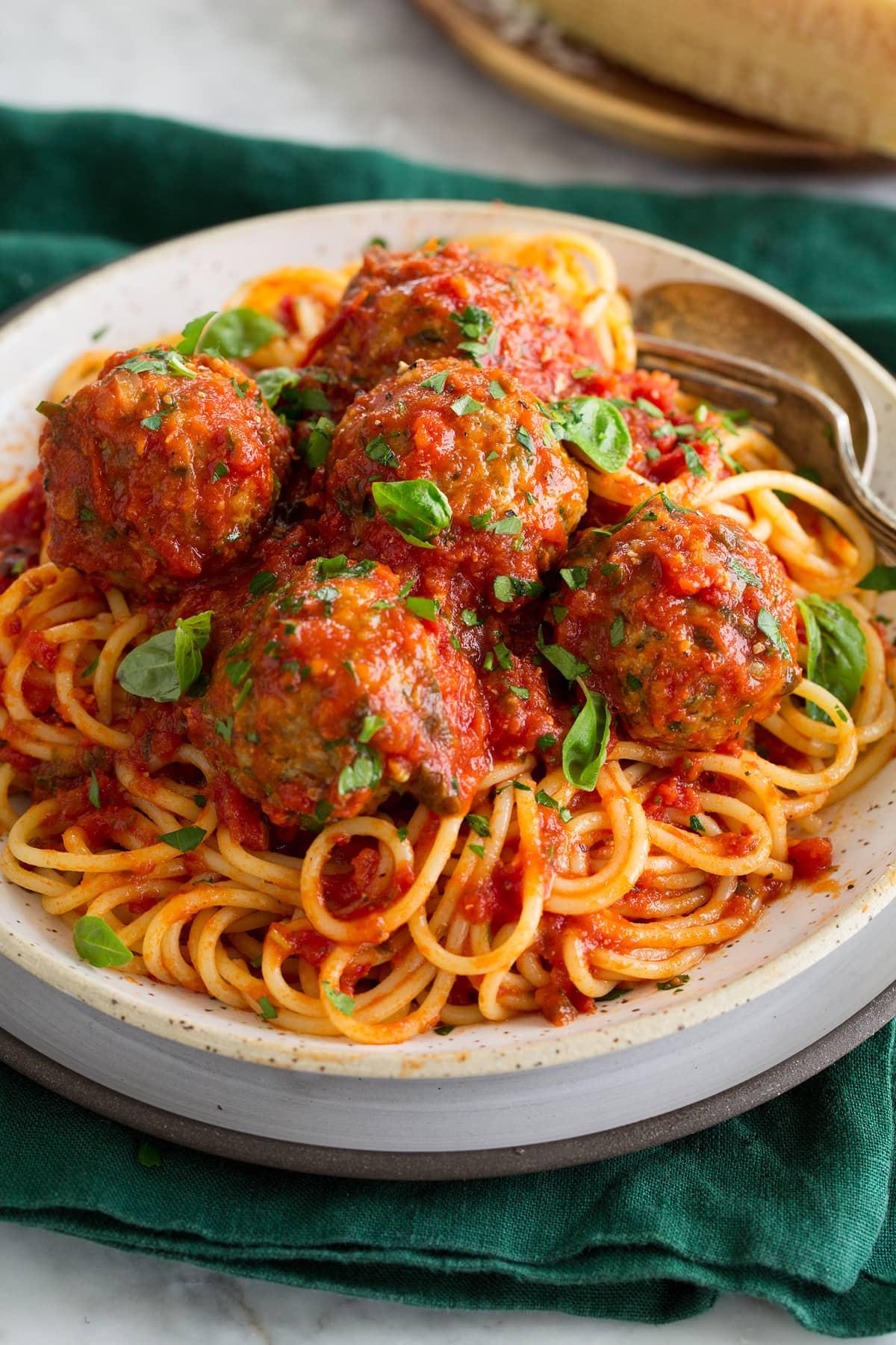 Turkey meatballs and marinara sauce shown over spaghetti pasta.