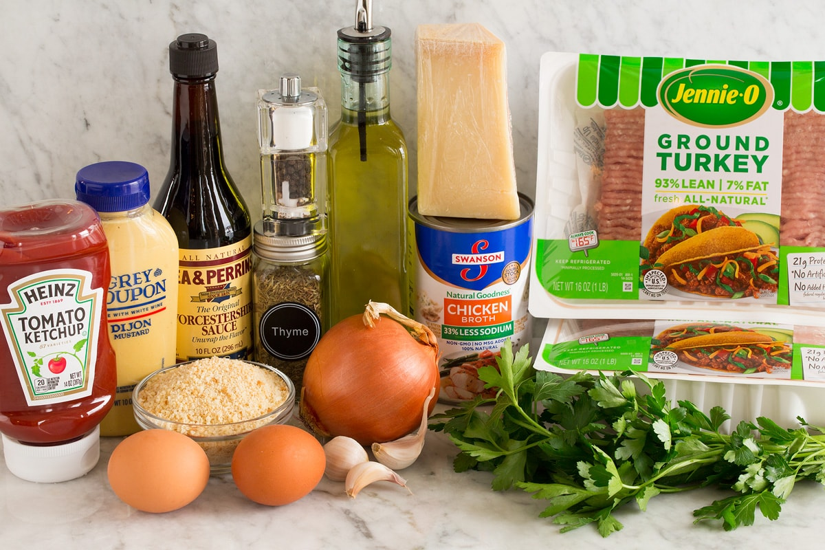 Photo of ingredients used in turkey meatloaf. Includes ground turkey, parsley, parmesan, chicken broth, olive oil, yellow onion, garlic cloves, eggs, bread crumbs, thyme, salt and pepper, Worcestershire, dijon, ketchup.