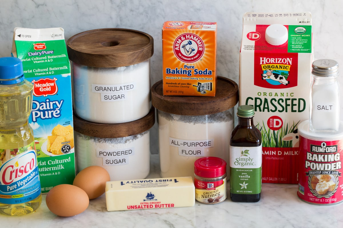 Photo of ingredients used to make baked donuts. Includes vegetable oil, buttermilk, eggs, butter, flour, powdered sugar, granulated sugar, nutmeg, vanilla extract, baking soda, baking powder, salt and milk.