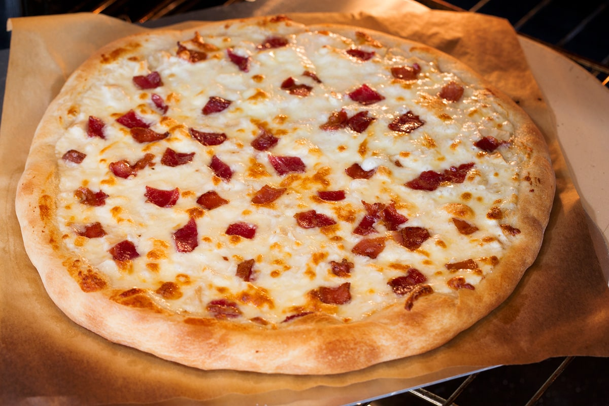 Photo of alfredo pizza being baked in the oven.