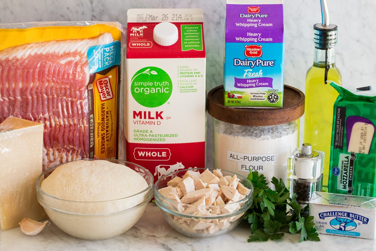 Photo of ingredients for making chicken alfredo pizza. Includes bacon, parmesan, pizza dough, garlic, chicken, parsley, flour, heavy cream, milk, olive oil, mozzarella cheese and butter.