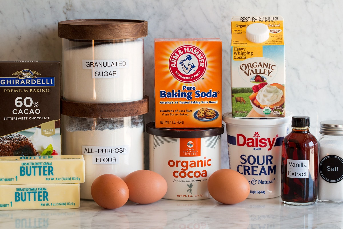 Photo of ingredients used for chocolate bundt cake. Includes flour, sugar, butter, chocolate, eggs, cocoa powder, baking soda, cream, sour cream, vanilla and salt.