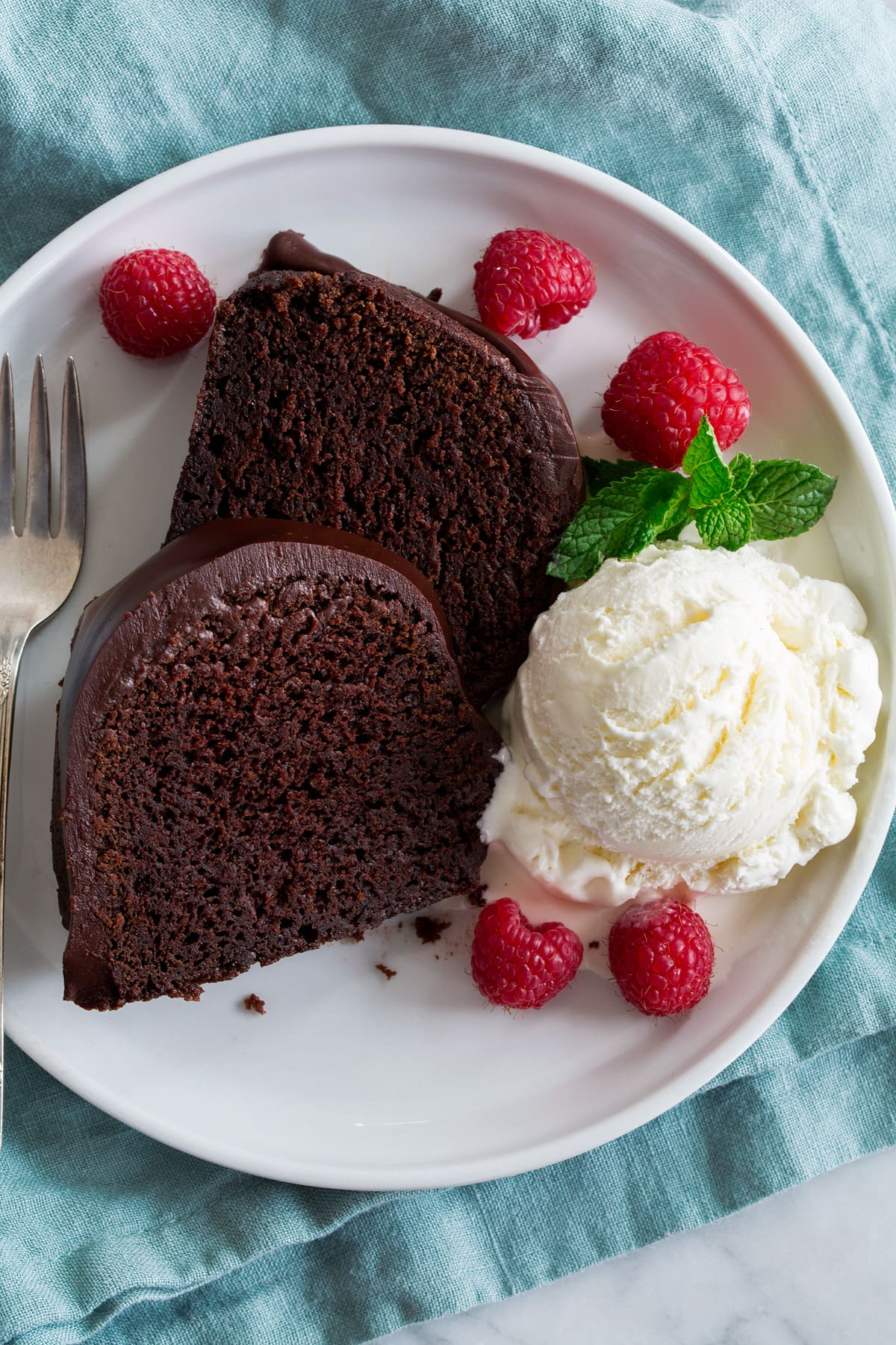 Two slices of chocolate bundt cake on a white plate with a scoop of vanilla ice cream, raspberries and mint to the side.
