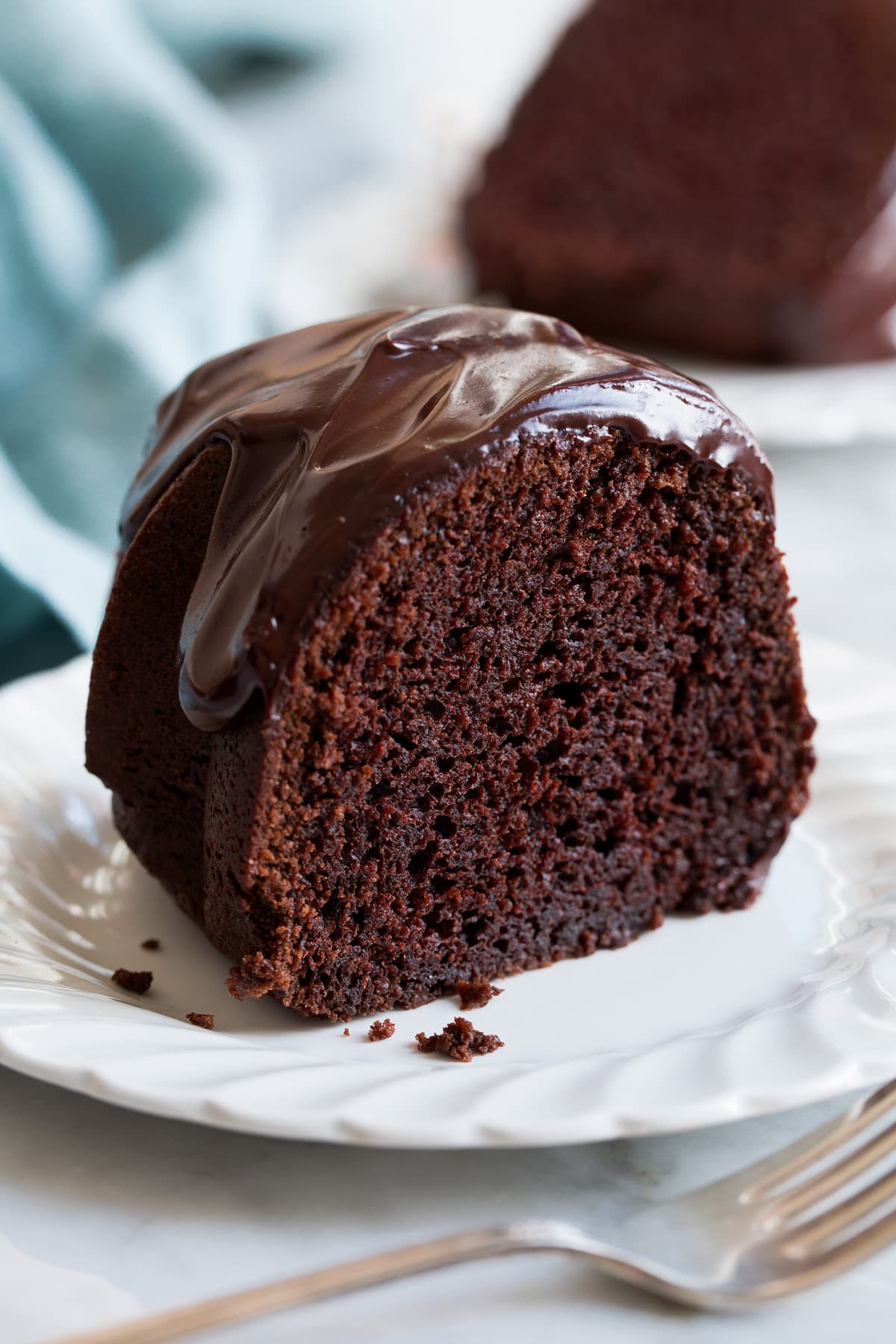 Slice of chocolate bundt cake covered with chocolate ganache.