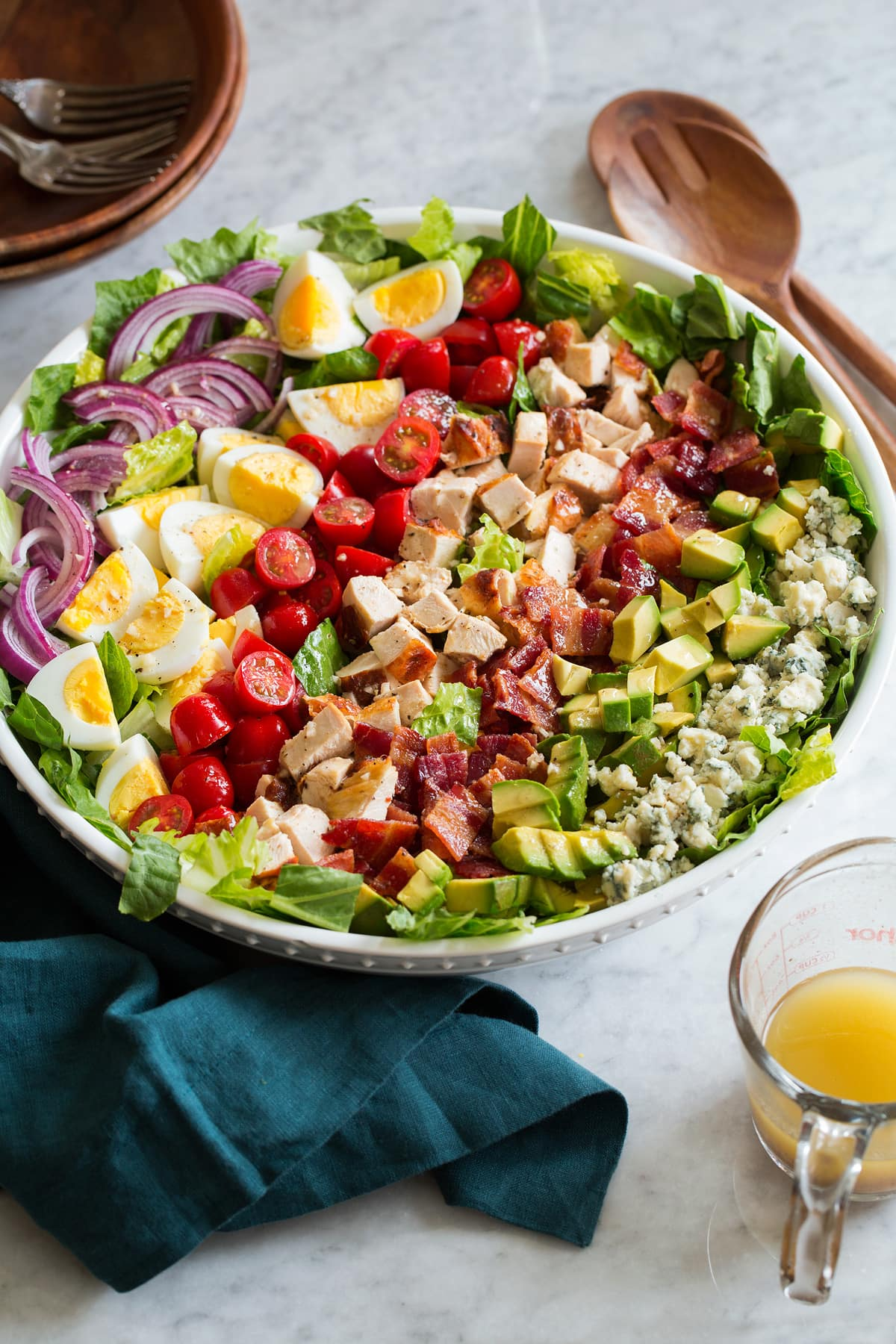 Cobb salad shown from the side on a marble surface.