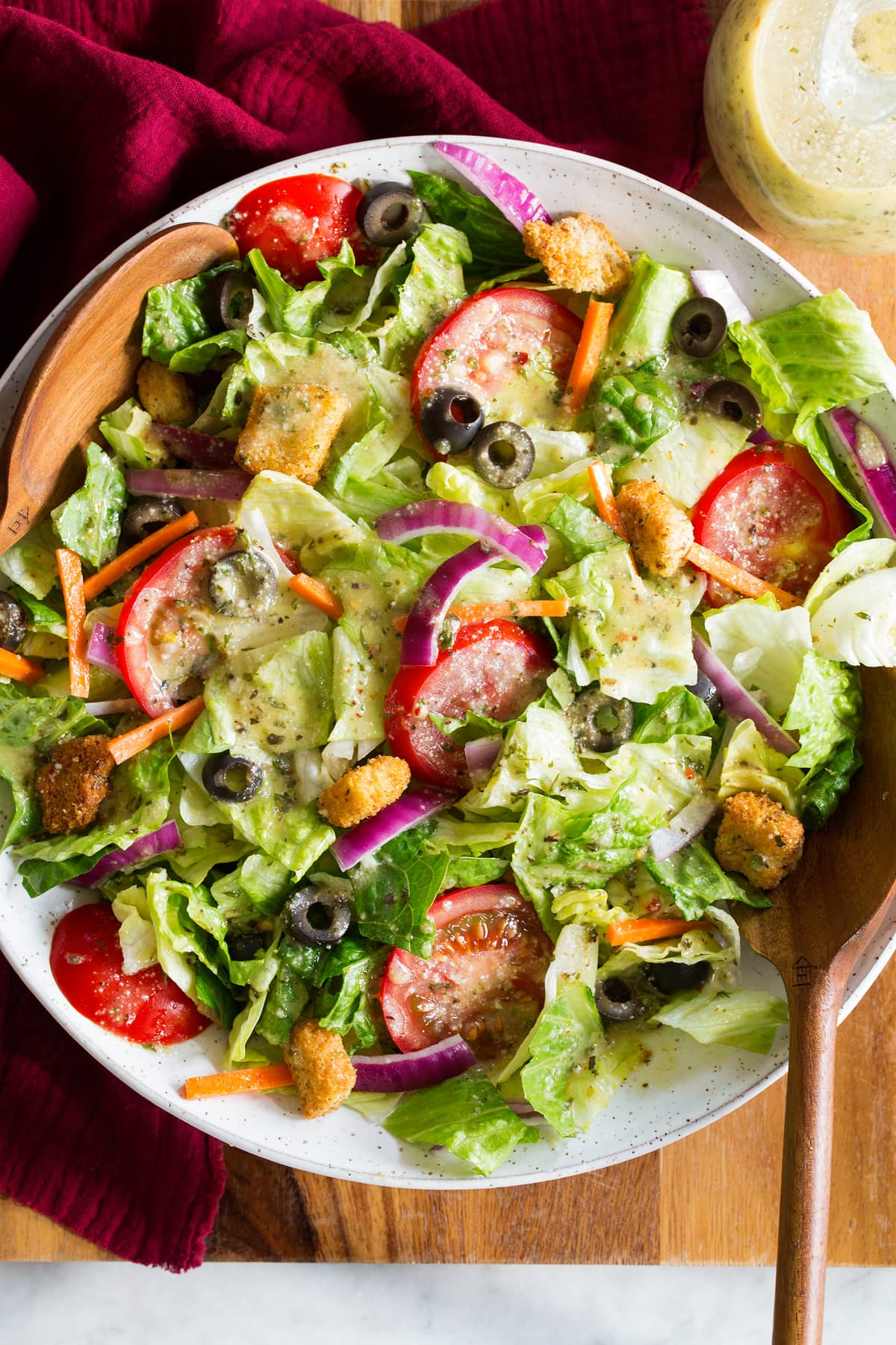 Photo: Green iceberg and romaine salad with carrots, olives and tomatoes that has been topped with Italian salad dressing.
