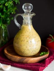 Photo: Italian Dressing in a glass bottle set over a wooden plate and a red cloth.