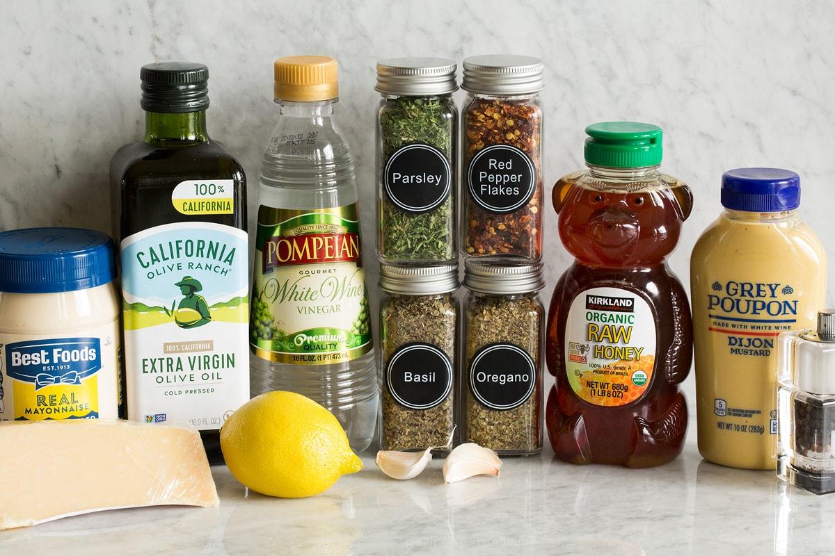 Photo of ingredients used in making homemade Italian dressing. Includes mayonnaise, parmesan, olive oil, lemon, white wine vinegar, parsley, basil, oregano, red pepper flakes, garlic, honey, dijon mustard, salt and pepper.