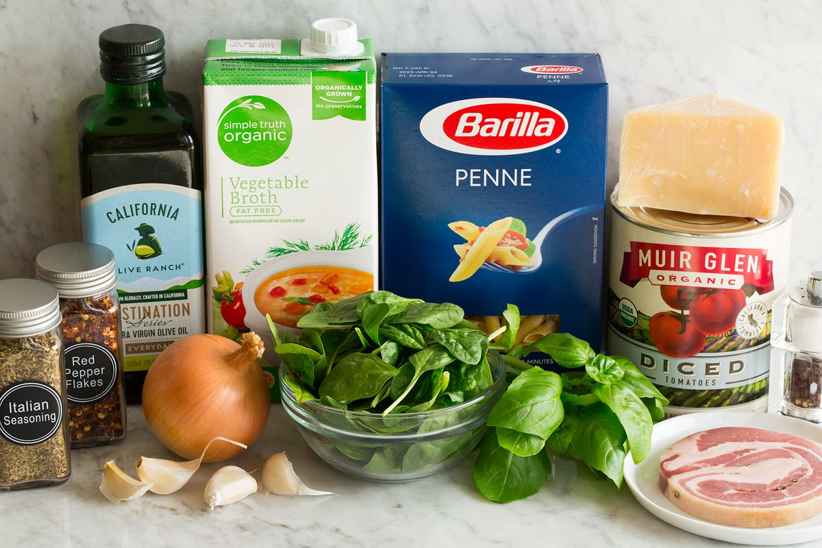 Photo of Ingredients used to make one pot pasta. Includes penne pasta, parmesan, canned tomatoes, spinach, basil, Italian seasoning, pancetta, basil, yellow onion, garlic, red pepper flakes, olive oil and vegetable broth.