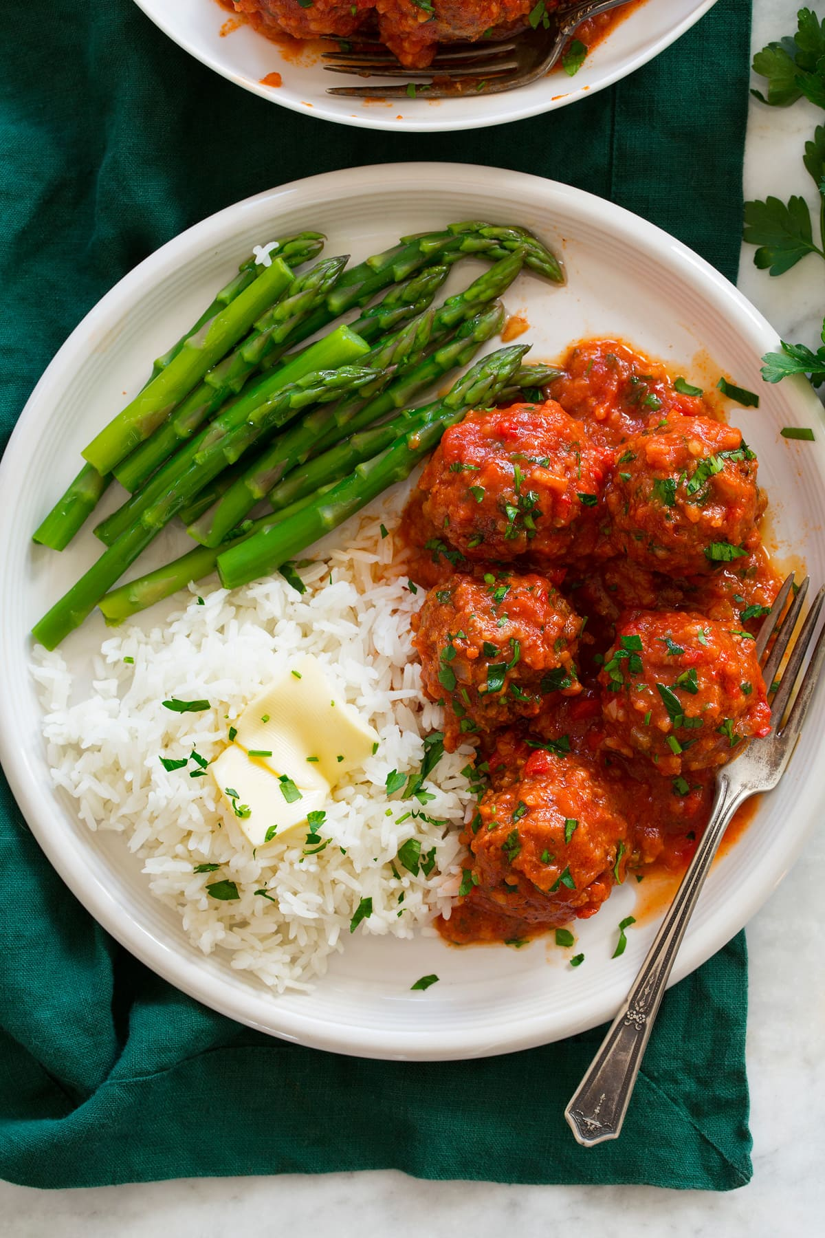 Overhead photo of Porcupine Meatballs meatballs on a plate with rice and asparagus.