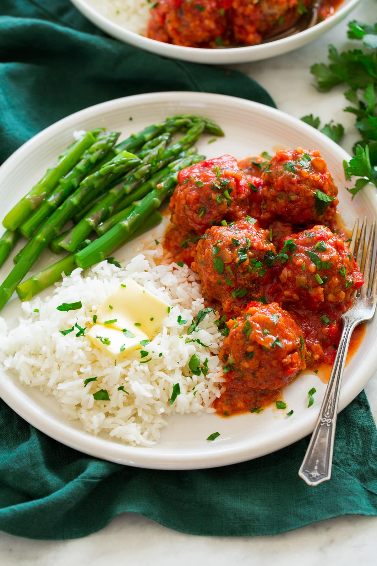 Porcupine Meatballs shown on a large white plate with sides of rice and butter and steamed asparagus.