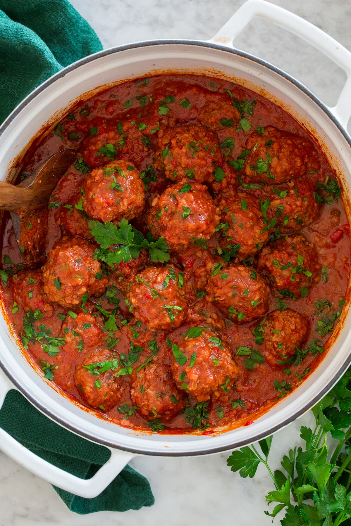Overhead photo of Porcupine Meatballs in tomato sauce in a large white pot set over a marble surface with a green cloth to the side.
