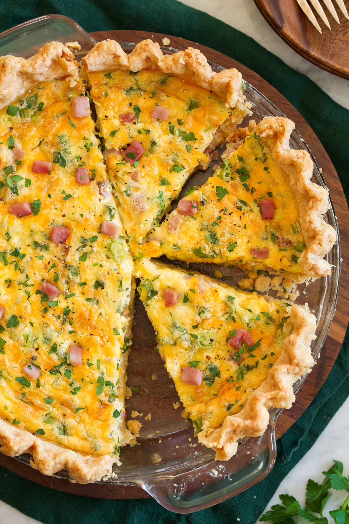 Overhead photo of sliced quiche in a glass pie pan.