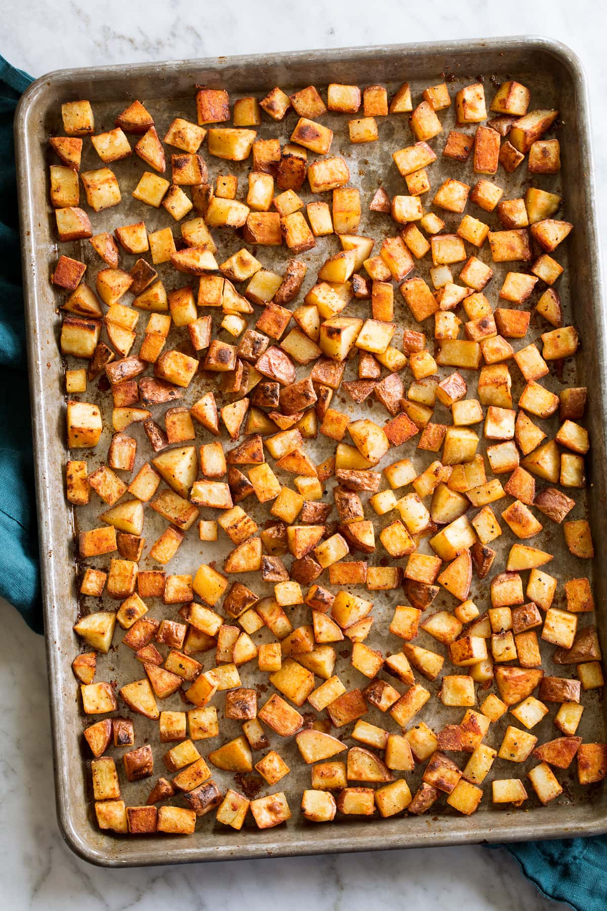 Photo: Crispy browned breakfast potatoes on a sheet pan set on a white marble surface.