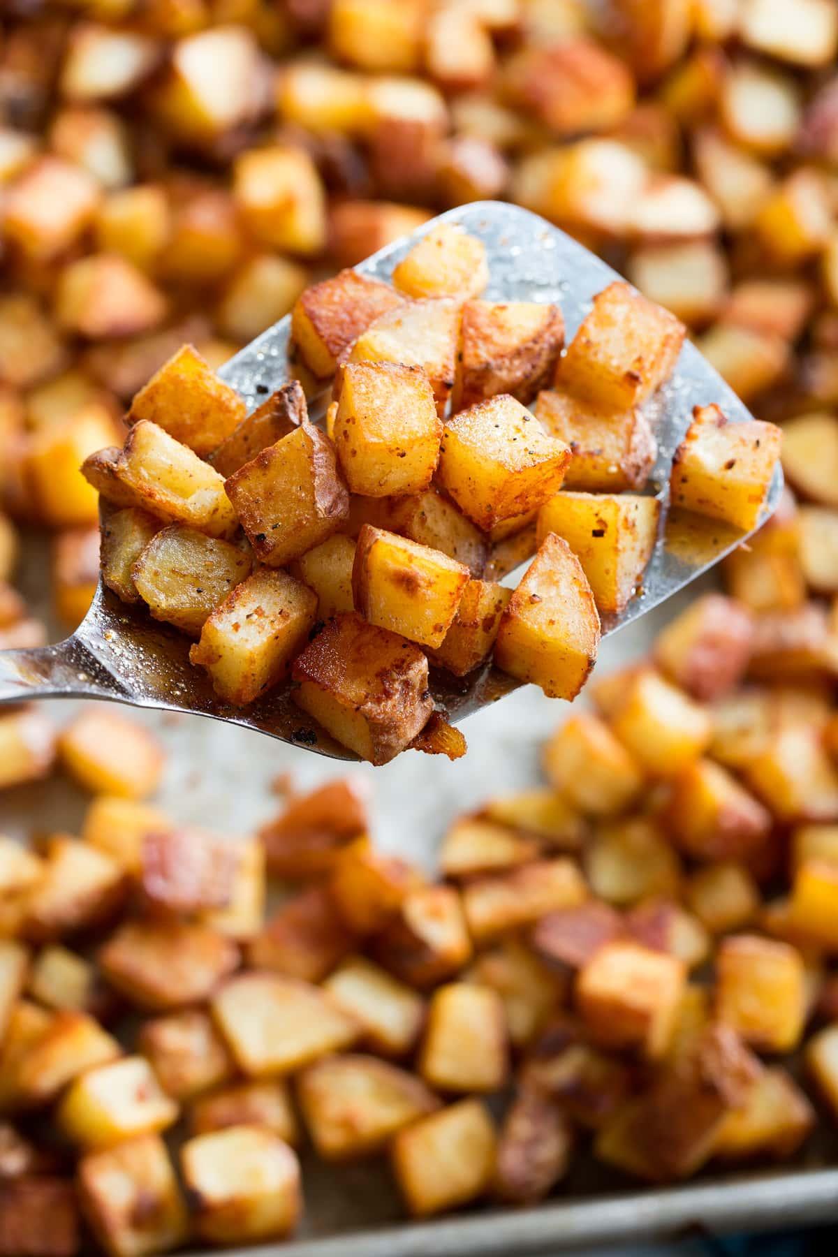Photo: Close up of breakfast potatoes on a metal spatula.