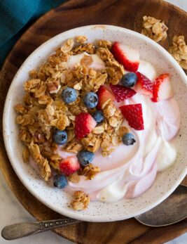 Granola, yogurt and fruit bowl shown from above.