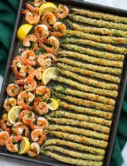 Photo of sheet pan filled with a row of garlic lemon butter shrimp on the left side and panko parmesan crusted asparagus on the ride side. Shown from overhead.