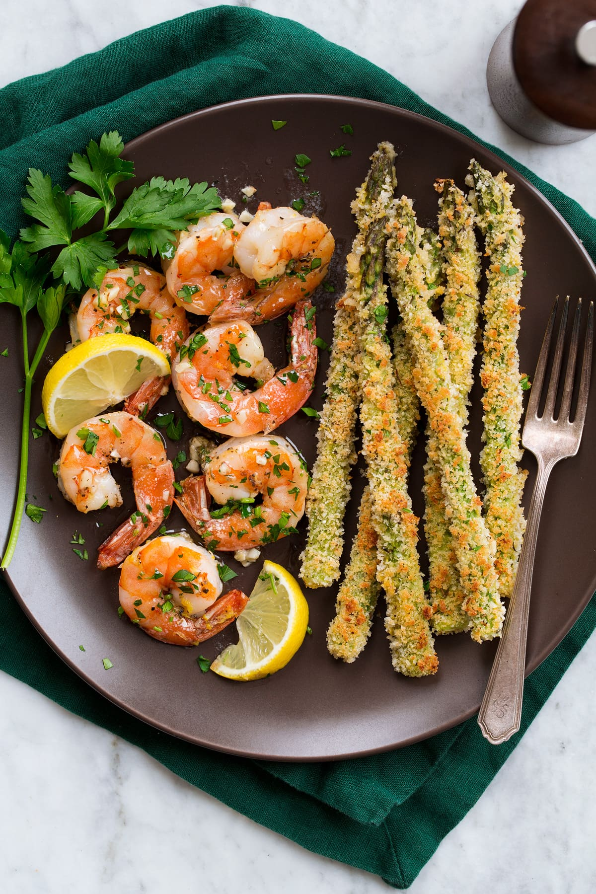 Overhead photo of buttery garlic shrimp and panko asparagus on a dark brown plate set over a dark green cloth napkin.