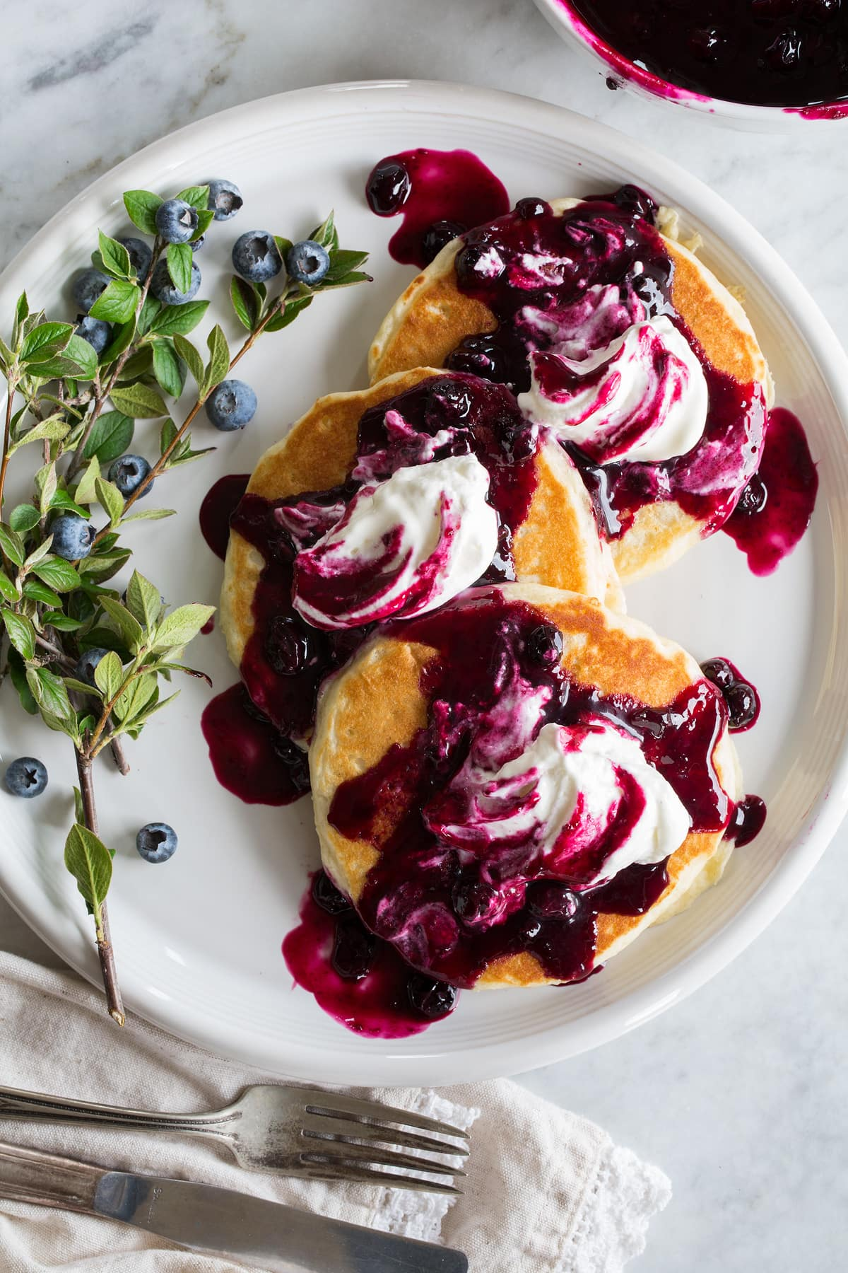 Blueberry syrup shown poured over pancakes with whipped cream on top.