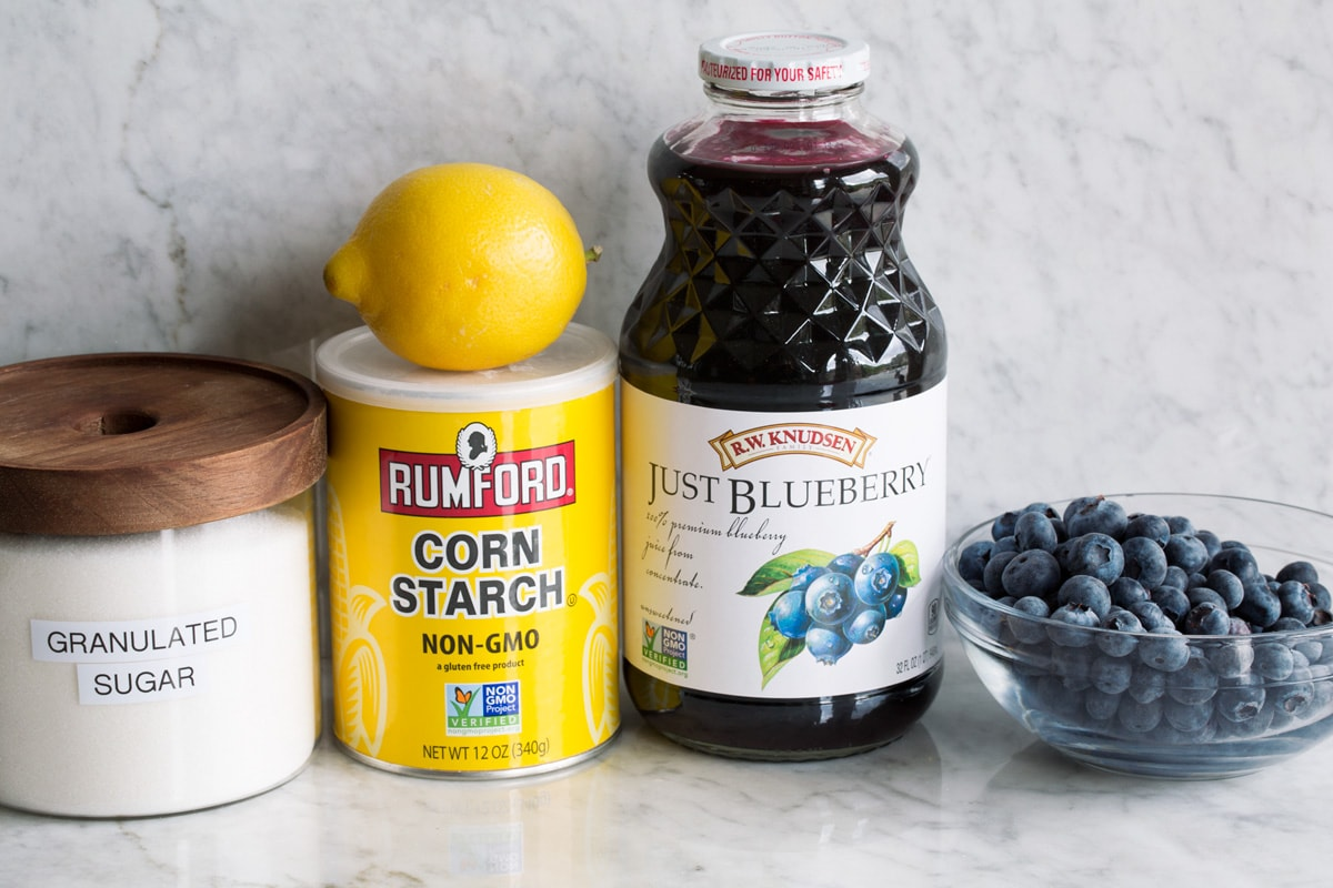 Ingredients used to make blueberry syrup. Includes blueberries, blueberry juice, cornstarch, lemon and sugar.