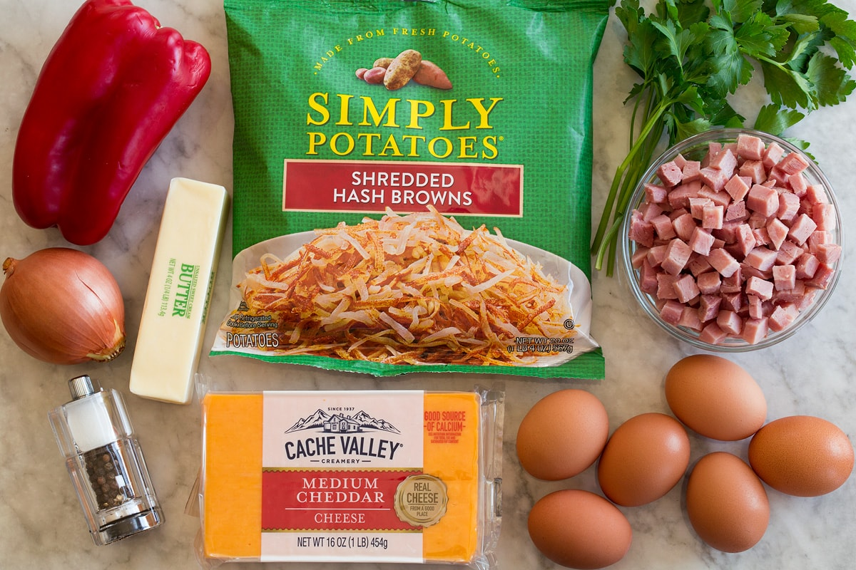 Photo: Ingredients shown that are used to make breakfast hash. Includes packaged shredded hash browns, bell pepper, cheddar cheese, eggs, butter, onion, ham, parsley, salt and pepper.