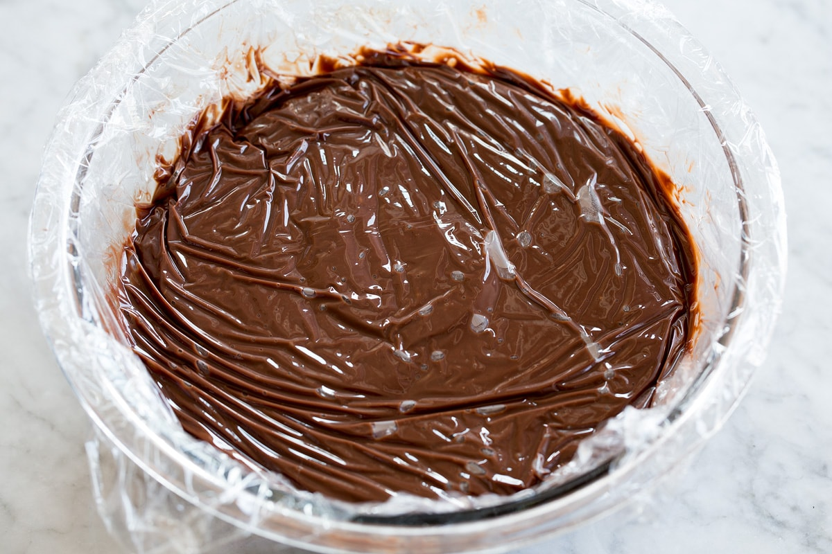 Chocolate pudding in a glass bowl with plastic wrap pressed against surface to prevent a skin from forming.