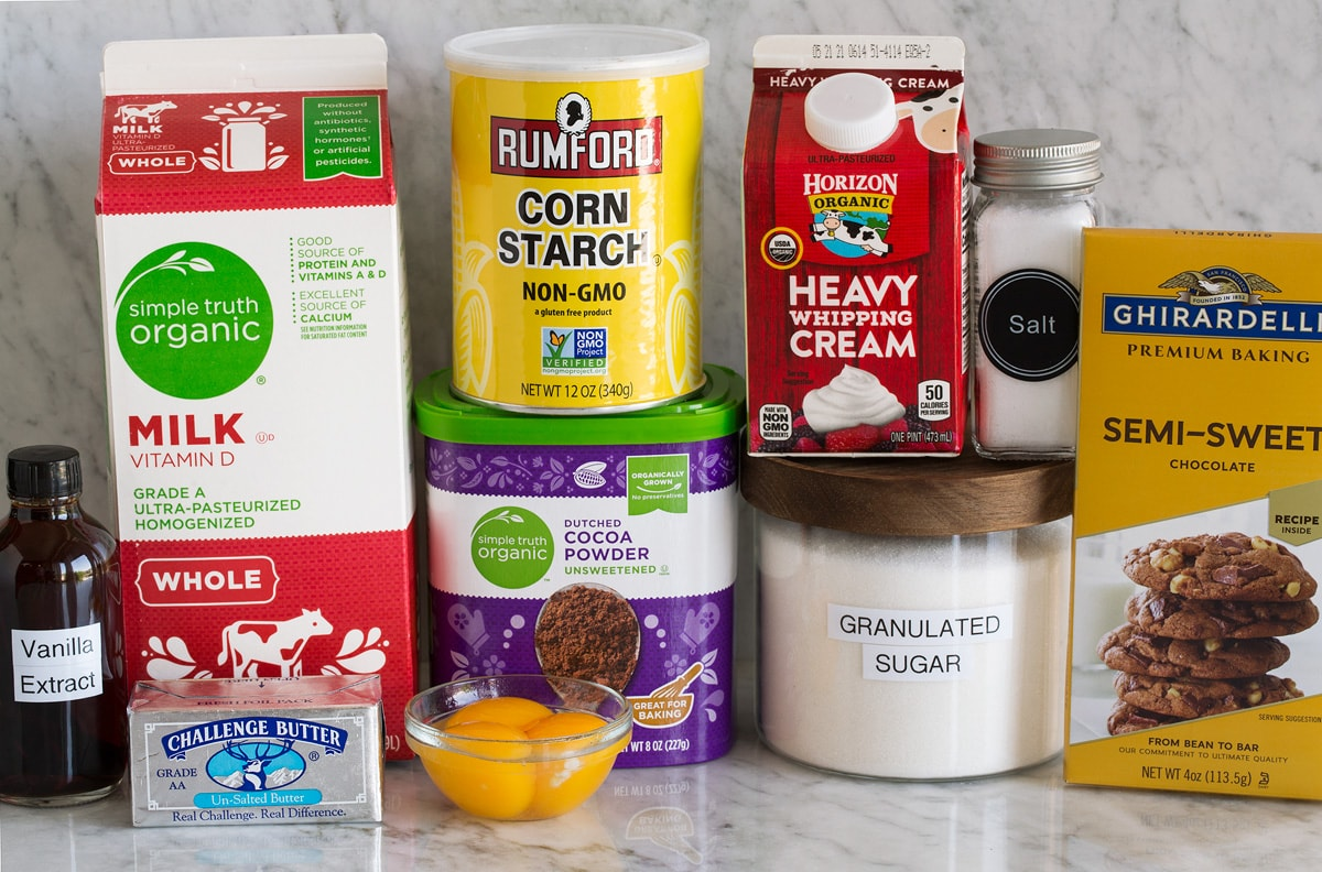 Photo of ingredients used to make chocolate pudding. Includes milk, butter, Dutch cocoa powder, egg yolks, cornstarch, sugar, salt, cream, chocolate, and vanilla.