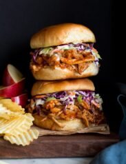 Photo: Two BBQ Pulled Chicken Sandwiches stacked on a wood platter. Apples slices and potato chips are shown to the side as serving suggestions.