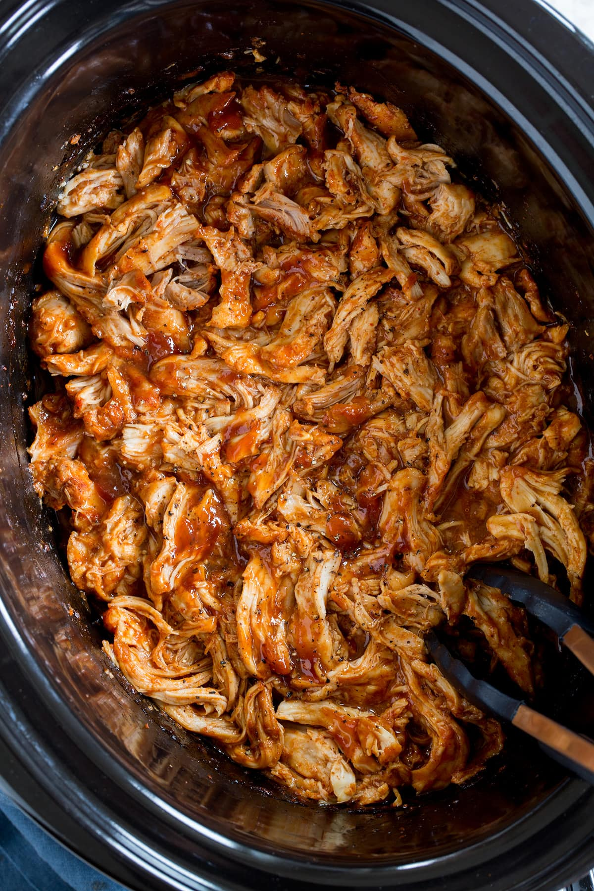 Photo: Slow cooker barbecue chicken in a black oval crockpot insert. Shown from overhead.
