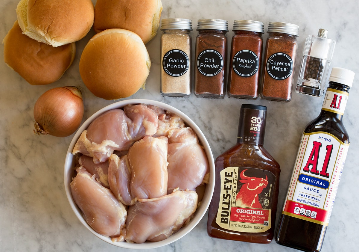 Photo: Ingredients used to make slow cooker barbecue chicken. Includes chicken thighs, bbq sauce, steak sauce, chili powder, smoked paprika, garlic powder, cayenne pepper, salt, pepper, buns, and yellow onion.