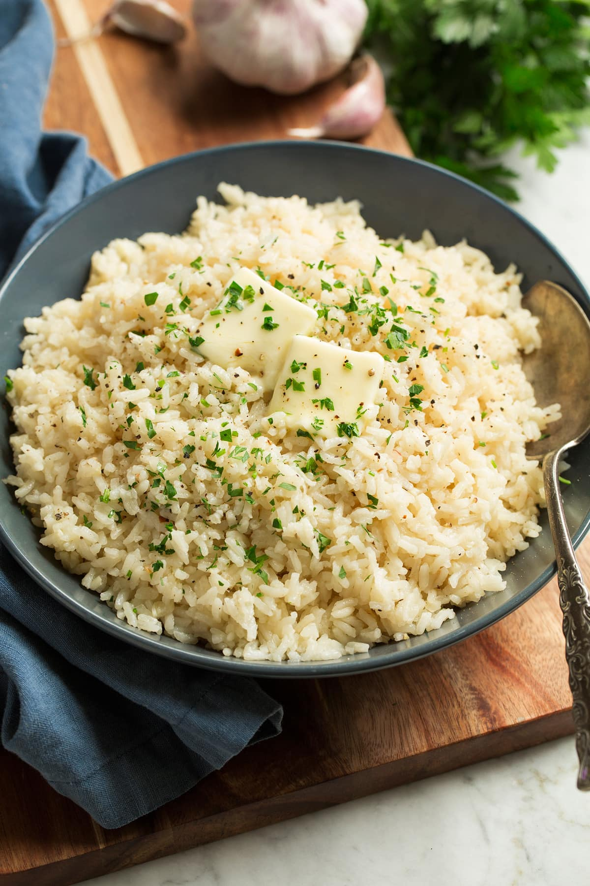 Rice seasoned with garlic and butter shown in a blue bowl over a wooden surface. Rice is topped with pieces of butter and chopped parsley.