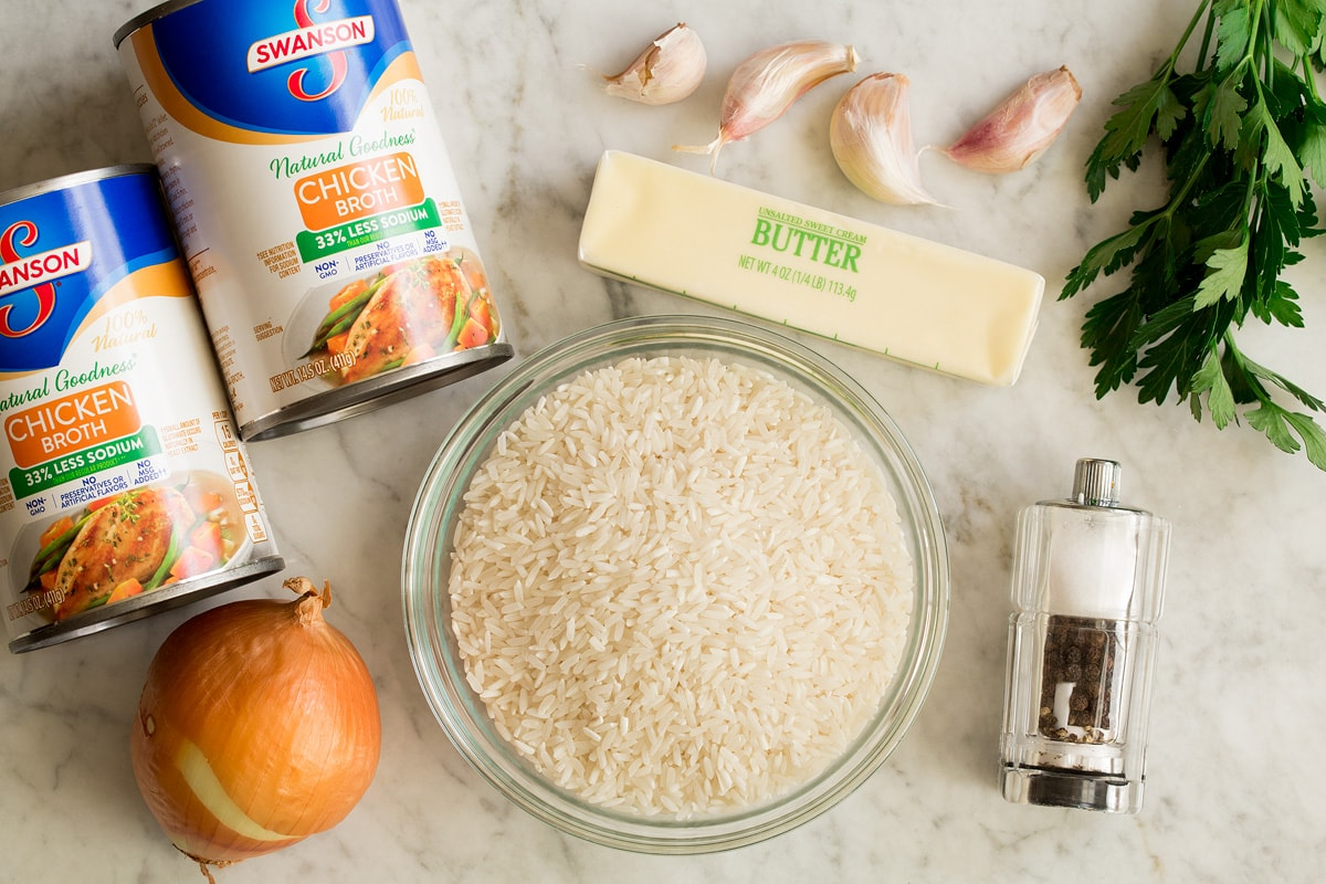 Photo of ingredients needed to make garlic butter rice. Includes white rice, chicken broth, onion, butter, garlic, parsley, salt and pepper.