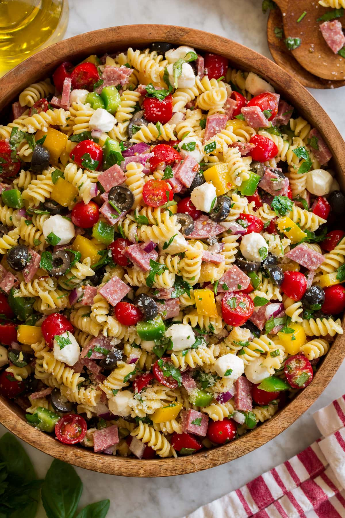 Photo: Italian Pasta Salad shown in a large wooden bowl from above. Bowl is resting on a marble surface with a striped cloth and jar of olive oil to the side.