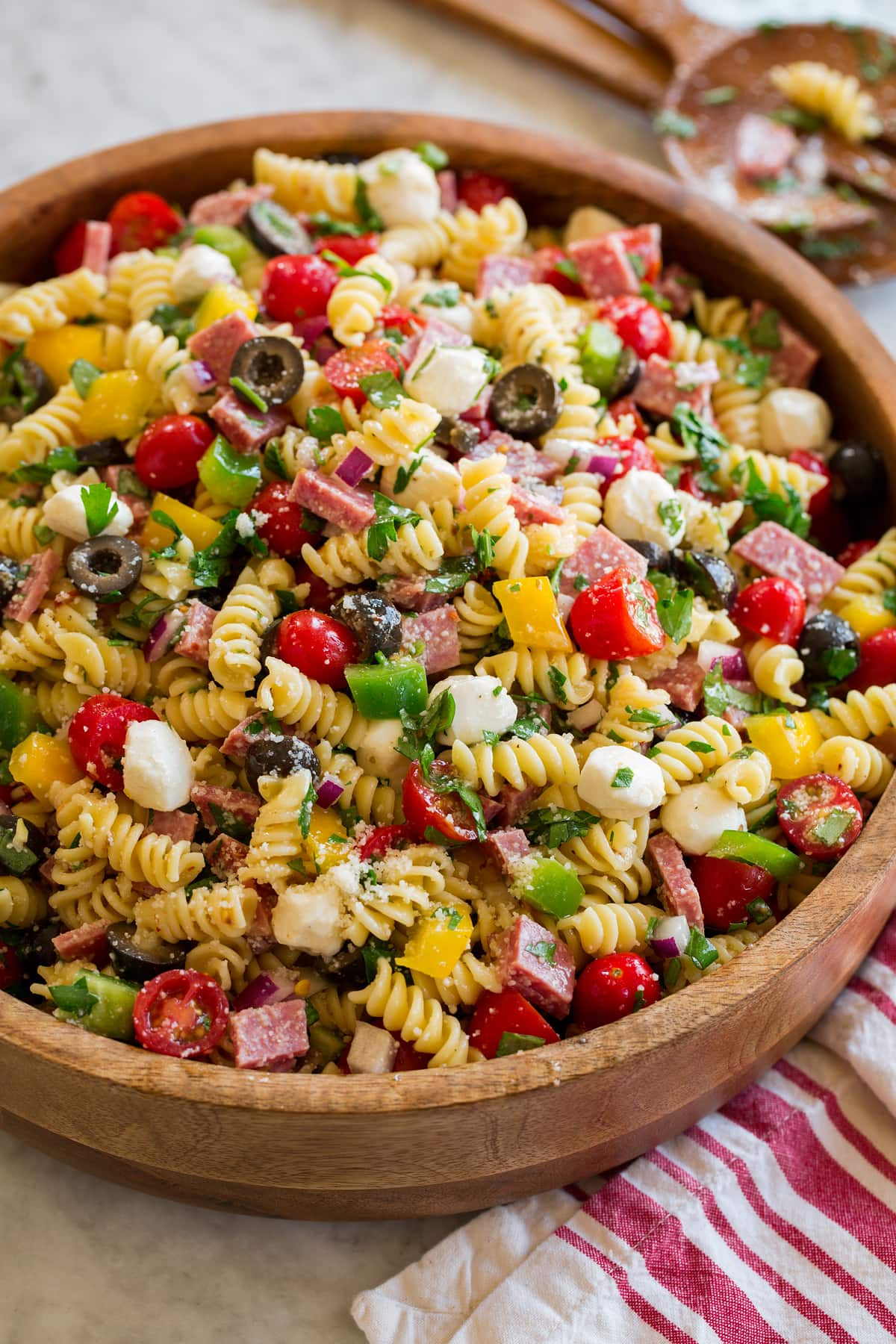 Italian pasta salad shown from a side angle on a large wooden bowl.
