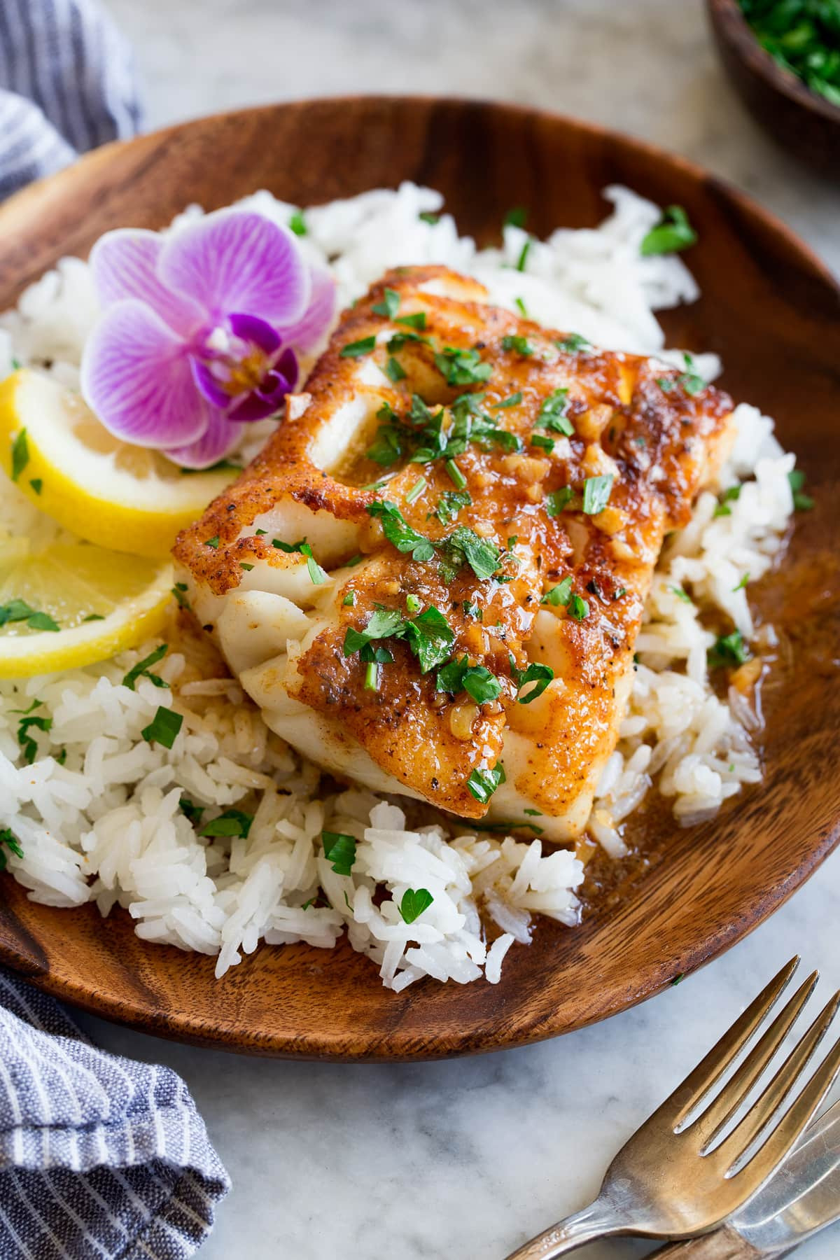 Photo: Pan seared cod fillet topped with a spice rub, lemon butter sauce and parsley. It is served over white rice with a purple flour and lemon slices to the side.