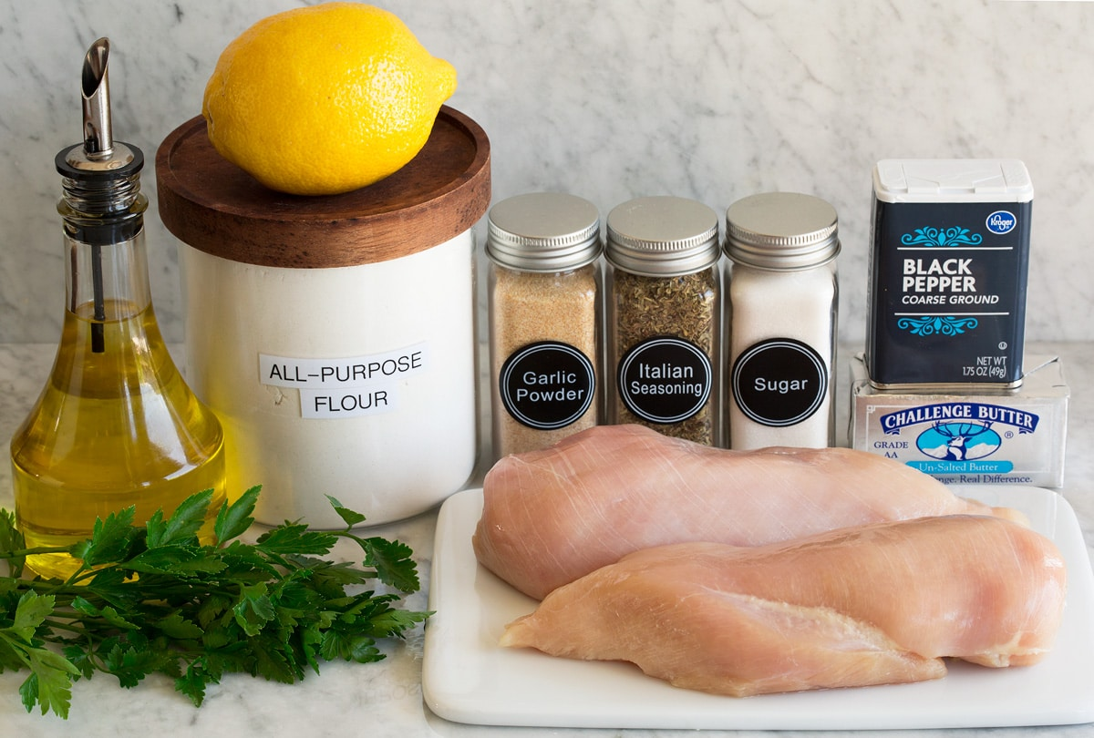 Photo of ingredients used to make lemon pepper chicken. Includes chicken breasts, butter, pepper, sugar, italian seasoning, garlic powder, flour, lemon juice, olive oil, and parsley.