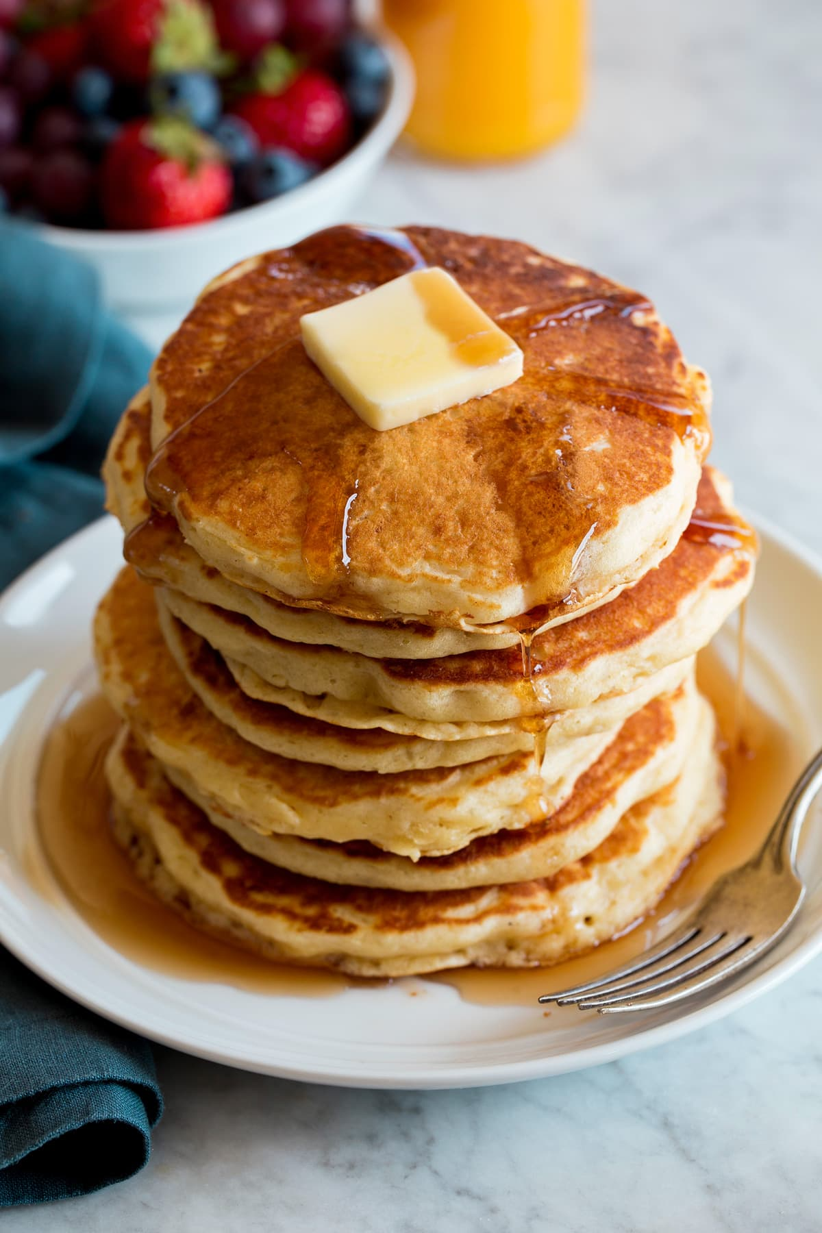 Stack of homemade pancakes on a white plate. Pancakes are topped with maple syrup and butter.