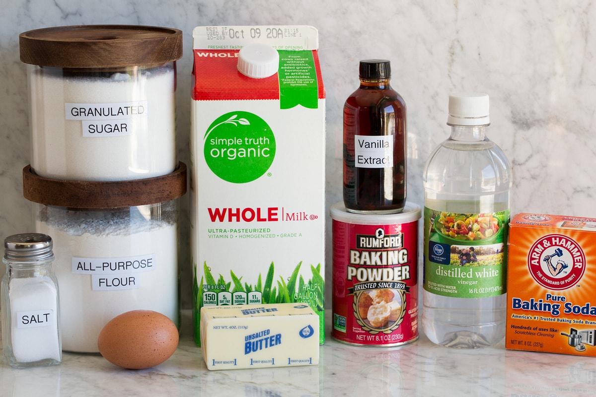 Photo of ingredients for pancakes. Includes milk, flour, sugar, baking soda, baking powder, vinegar, vanilla, sugar, egg and butter.