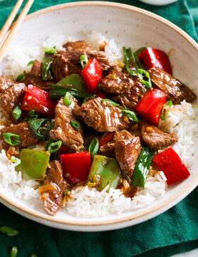 Photo: Pepper Steak in a bowl over white rice. Bowl is resting on a dark green cloth over a marble surface.