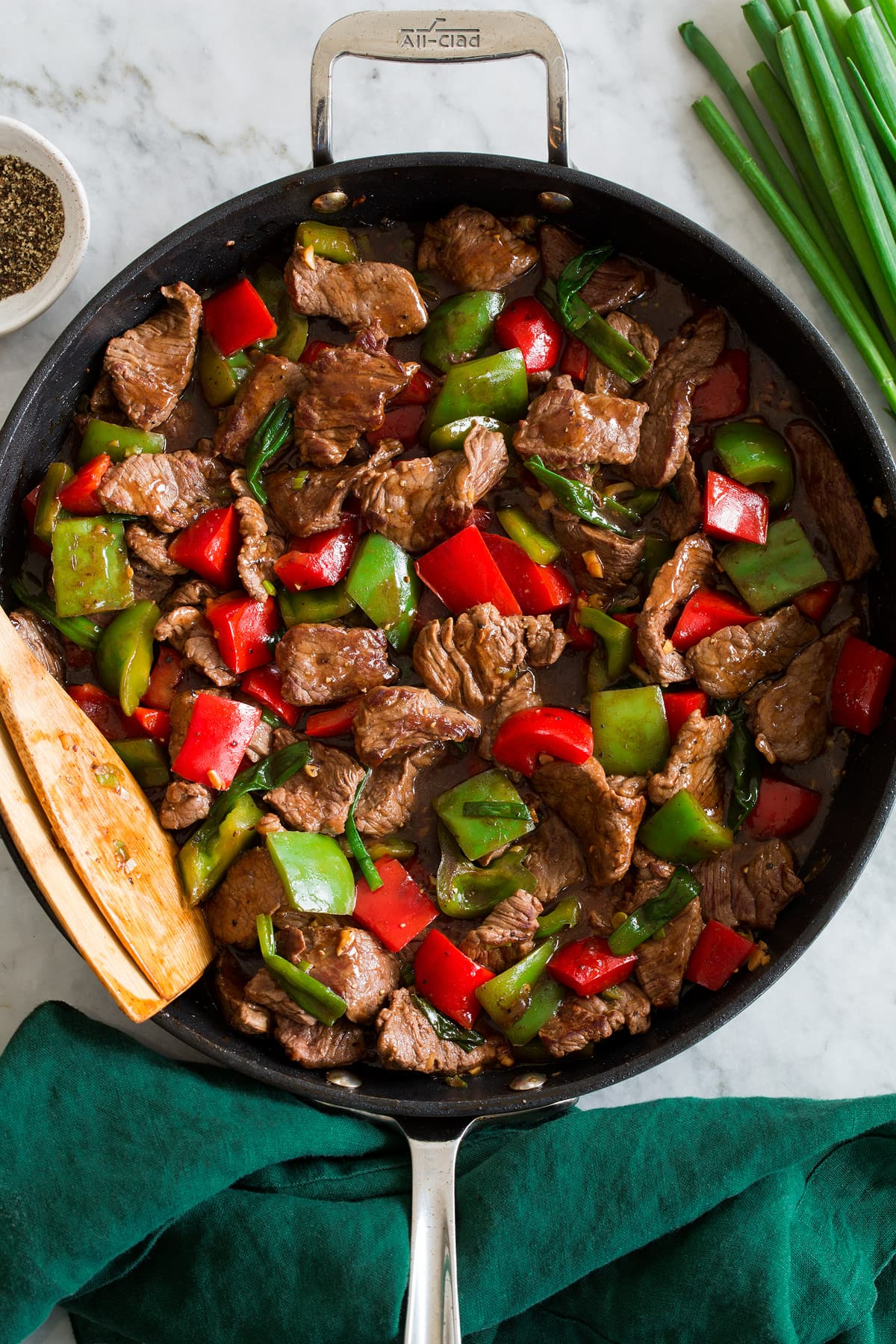 Photo: Pepper steak and bell peppers shown in a dark skillet from above.