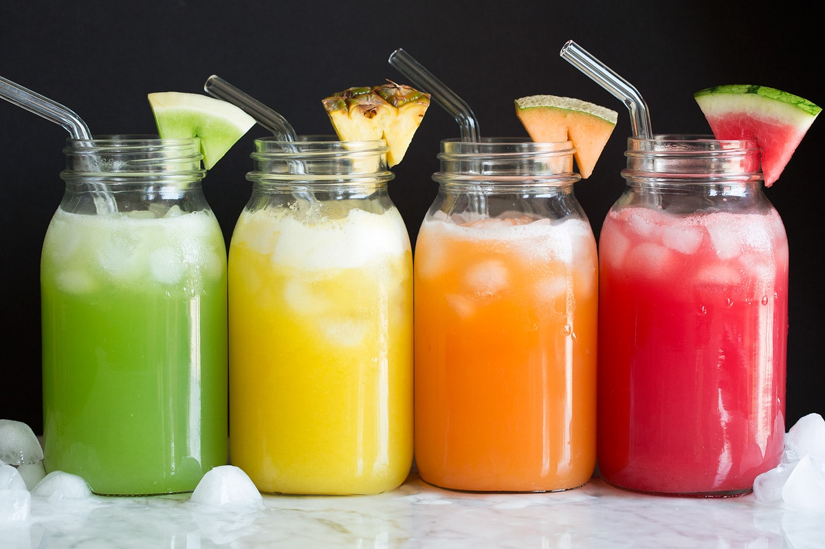 Photo: Four kinds of fruit aqua fresca shown in glass jars with glass straws and fruit wedge garnish.