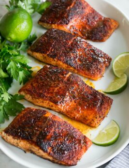 Photo: Blackened salmon shown topped with buttery honey lime sauce. Parsley and limes are shown as garnishes.