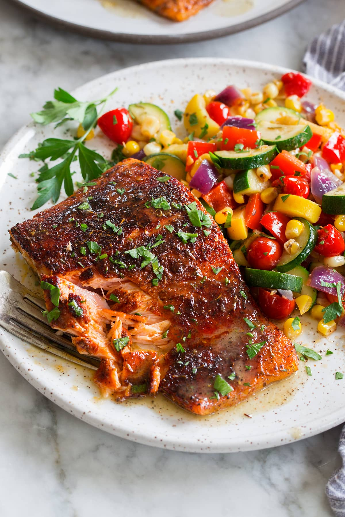 Close up photo of blackened salmon with buttery honey lime sauce. Sautéed vegetables are shown to the side as a serving suggestion.