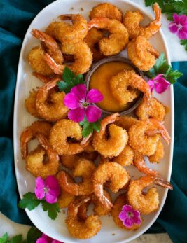 Photo: Many coconut shrimp spread out on a white oval platter with mango sauce in the center in a wooden cup. Vibrant pink flowers are dotted throughout for decoration and platter is resting on a blue cloth over a marble surface.