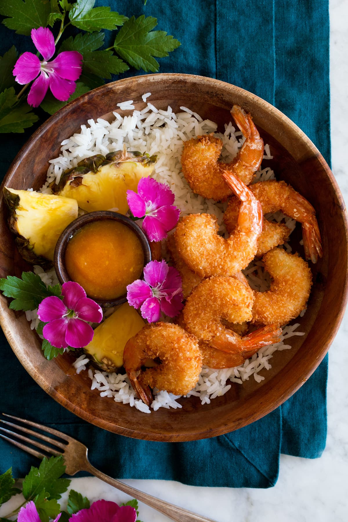 Photo: Coconut shrimp in a wooden bowl over coconut rice. It is served with a side of pineapple and bright pink flowers to the side.